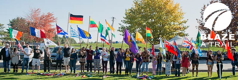 Knox College Students display the flags of their countries at a soccer game at the College