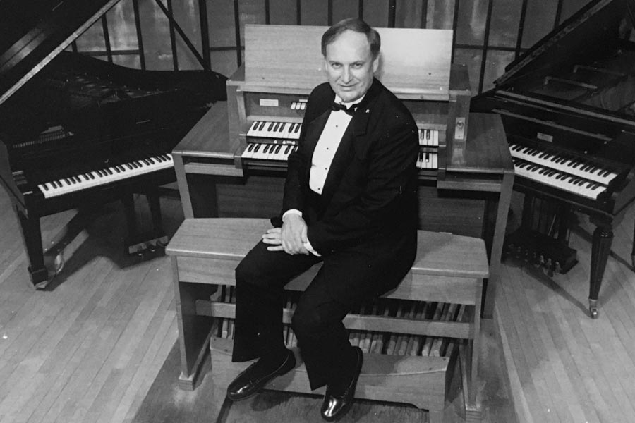 Charles Farley sits in front of several keyboard instruments, two organs and a piano.