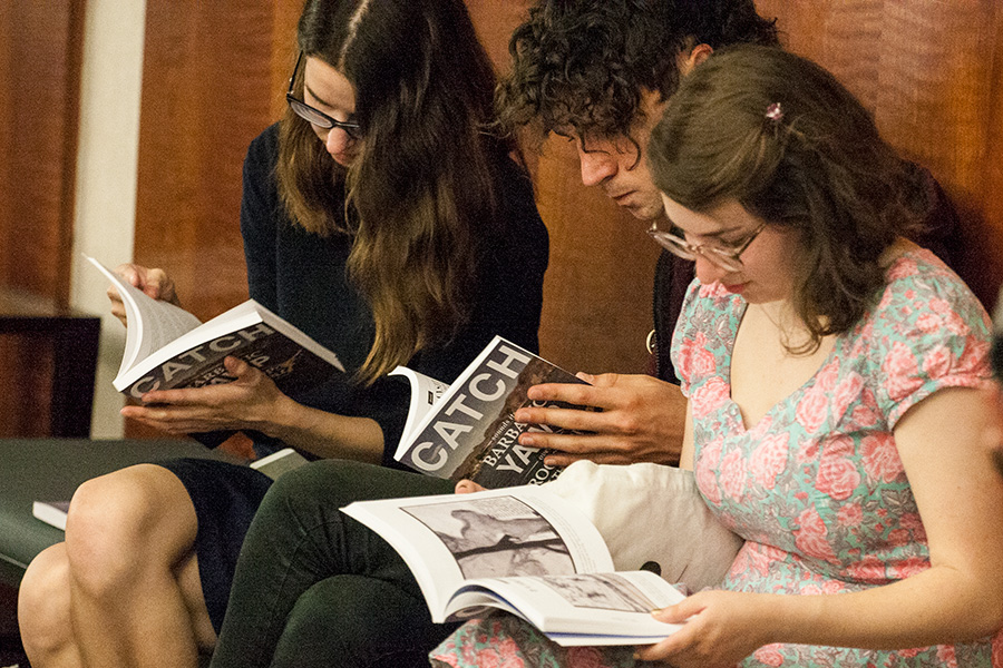 Students look over an issue of Catch at the release party.