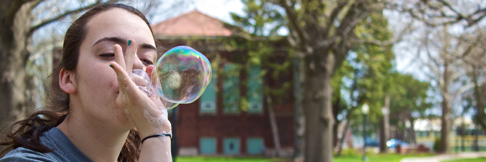 A student blows a bubble at the annual Earth Week Festival