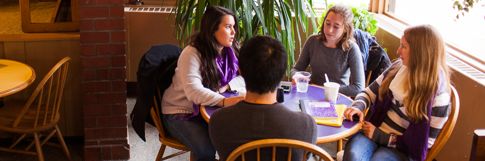 A group of students, talking at a table in the Gizmo.