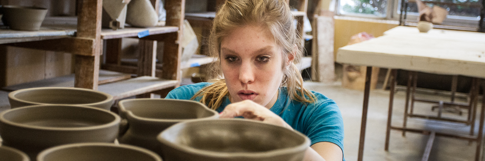 A student checks clay bowls as they dry in the ceramics studio.