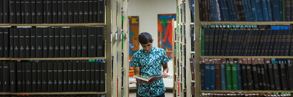 A student looks at a book in the shelves in Science Library.