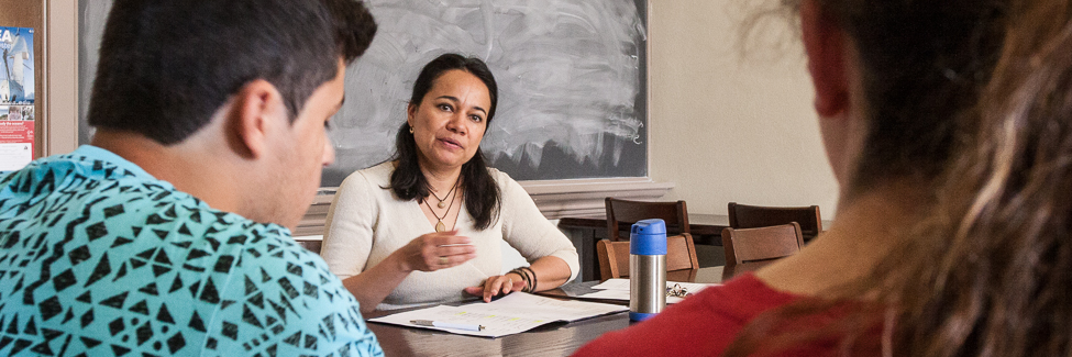 Professor Claudia Fernandez observes two students in a conversation-based exam.