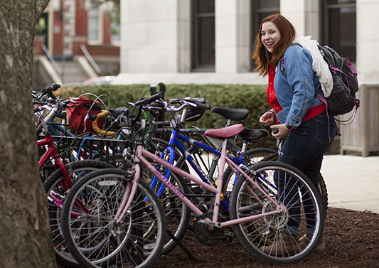 A student gets her bike from the bike rack outside of George Davis Hall.