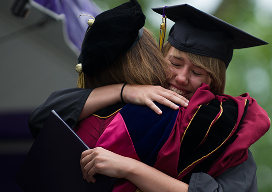 President Amott hugs a member of the Class of 2014 at Commencement.