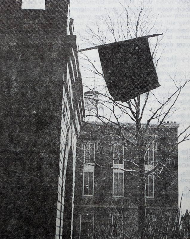 Photo of black flag on the brick tower.
