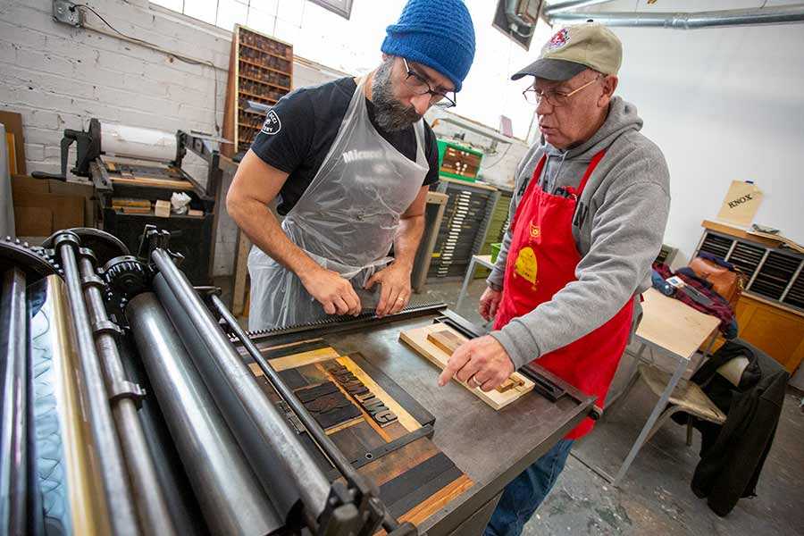Faculty member Nick Regiacorte and donor Hal Keiner '67 install letterpress equipment.