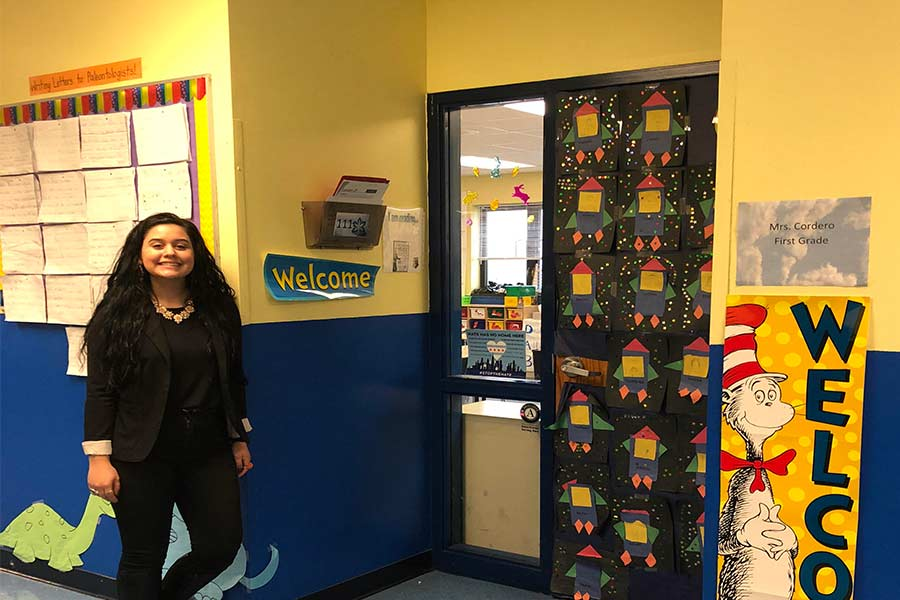 Stephanie Cordero '17 in front of her first grade classroom.