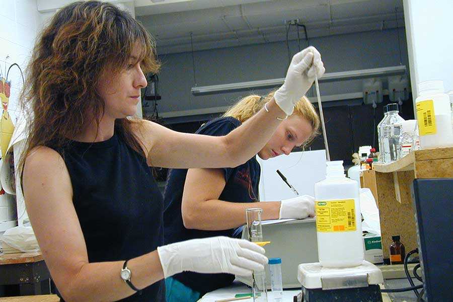 Janet Kirkley in a biochemistry lab with a student.