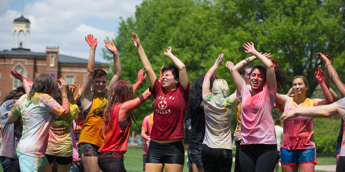 Students dance on the south lawn of Old Main to celebrate the Indian Holi festival.