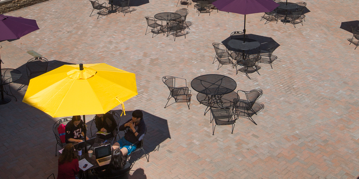 Students gather under a yellow umbrella on the Gizmo Patio.