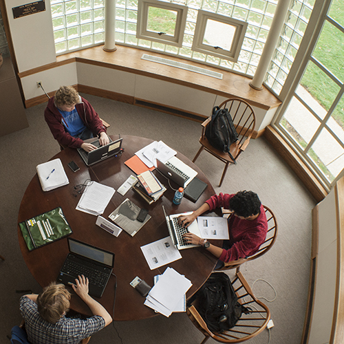 Students study around a table in the Seymour Library.