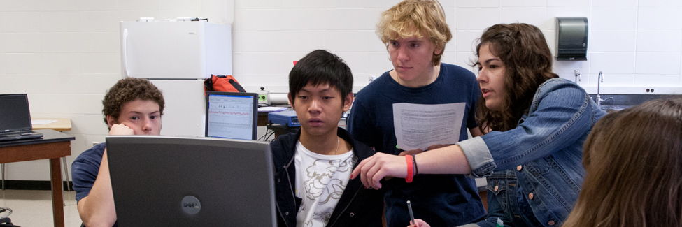 Students in a psychology class check data on a computer monitor.