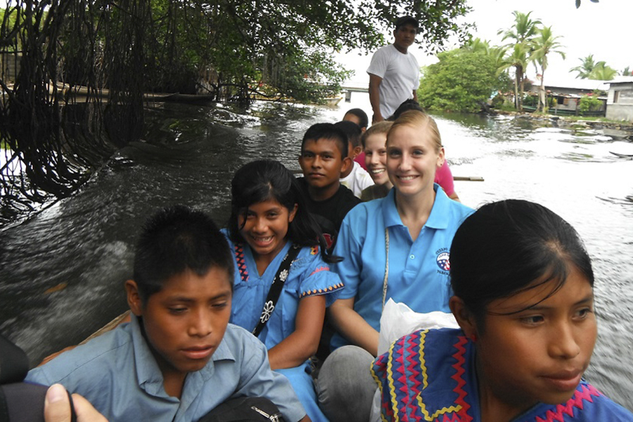 Alumna Katie Walker '11 sits in a boat with children during her time in Panama with the Peace Corps.