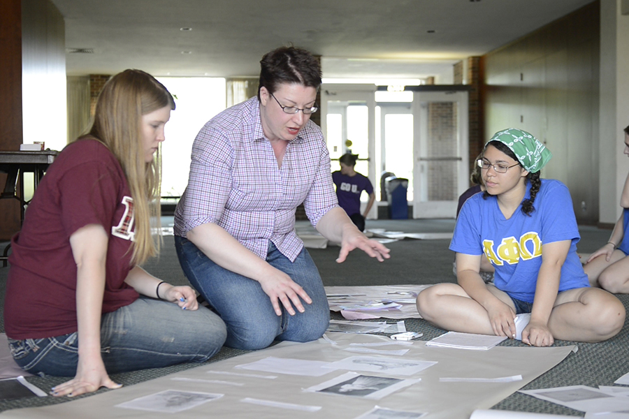 Professor Catherine Denial works with students in the lobby of Ford Center of Fine Arts.