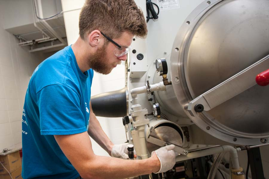 Knox College student Alex Volkov loads nitrogen-filled glove box for chemistry research.
