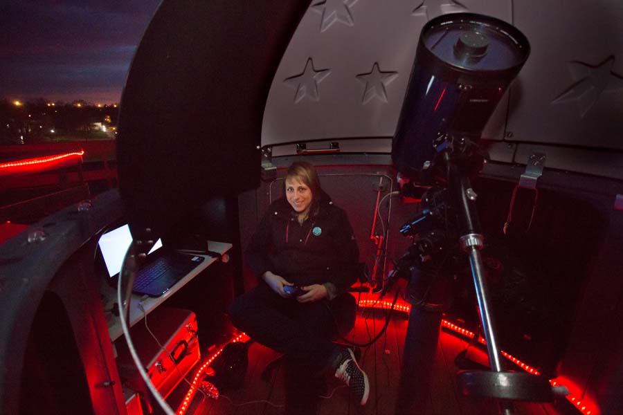 Knox College physics professor Nathalie Haurberg, with telescope, computer.