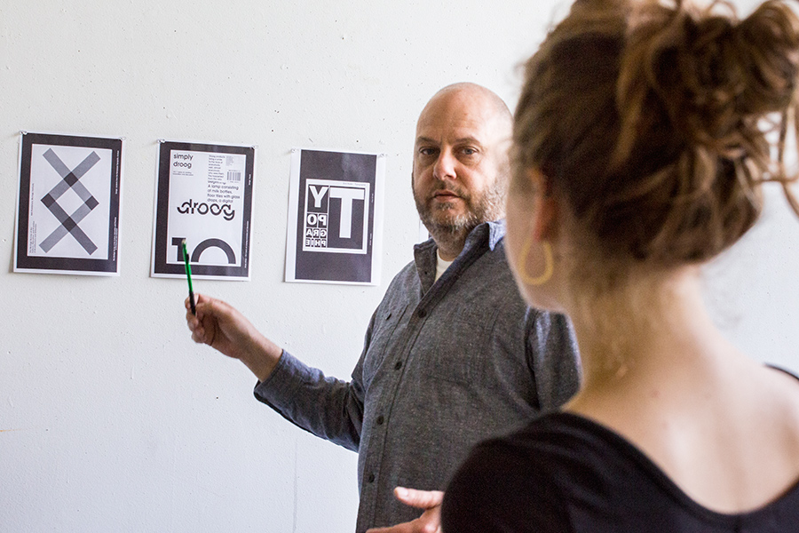 Visiting Assistant Professor of Art Tim Stedman discusses typography with a student during class.