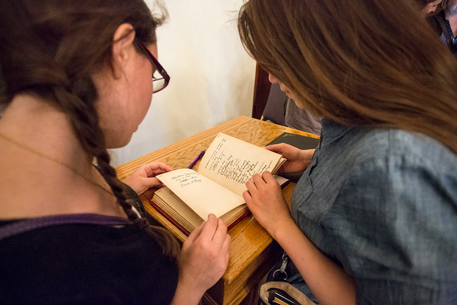 Students look at signatures in the Phi Beta Kappa book.