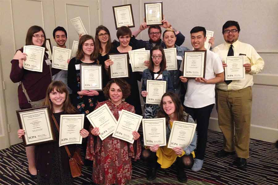 "The staff of ""The Knox Student"" holds up a record-breaking 20 awards at the most recent ICPA conference."