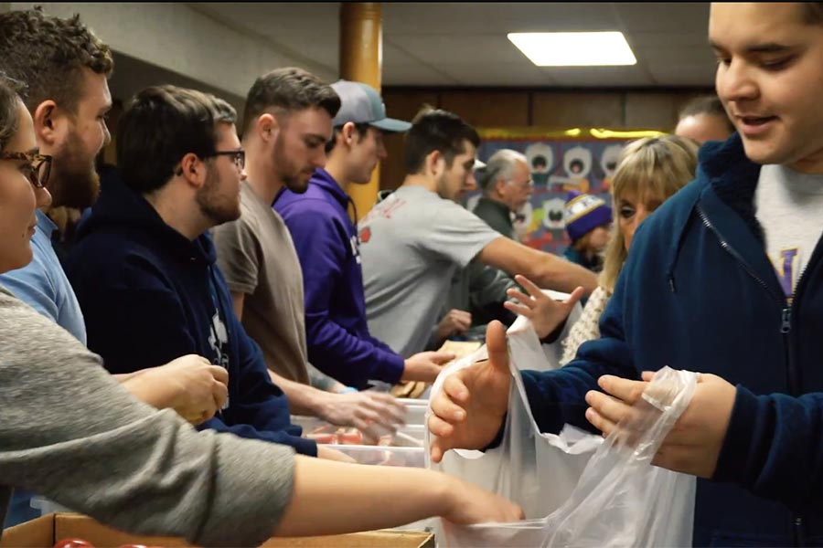 Knox College students bag food for elementary age children.