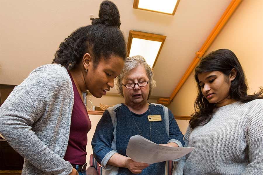 Students Avantika Gupta and  Aliya Estes (right) confer with Connie Pople, activities director at Seminary Manor and supervisor of their experience during Clinical Psychology Term.