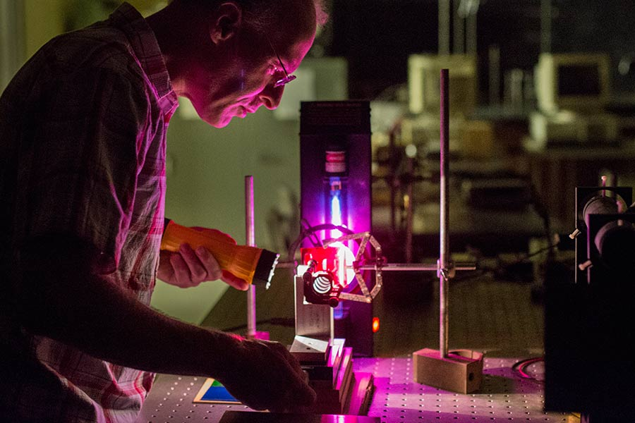 Physics professor Tom Moses adjusts a device used to analyze light -- Fabry-Perot interferometer -- that he and two students built in a physics department research lab.