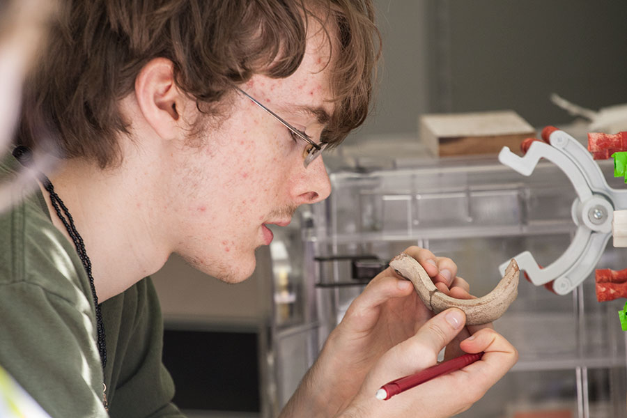 Student examines layers of ceramic artifact found at Dhiban site