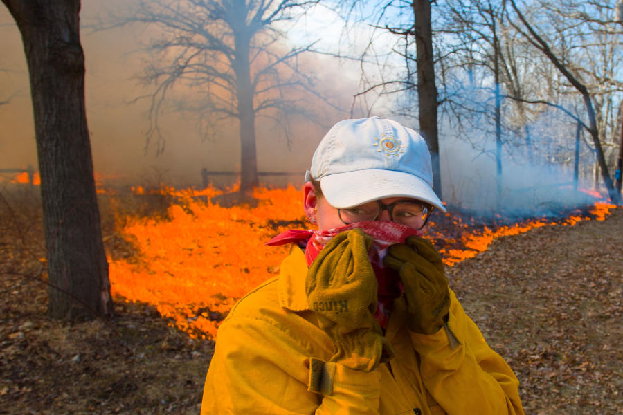 Knox College student turns away from the heat during the annual Prairie Burn at Green Oaks.