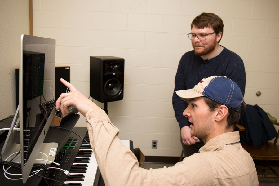 Pierce Gradone, standing, and Sam Beem in the Knox electronic music studio