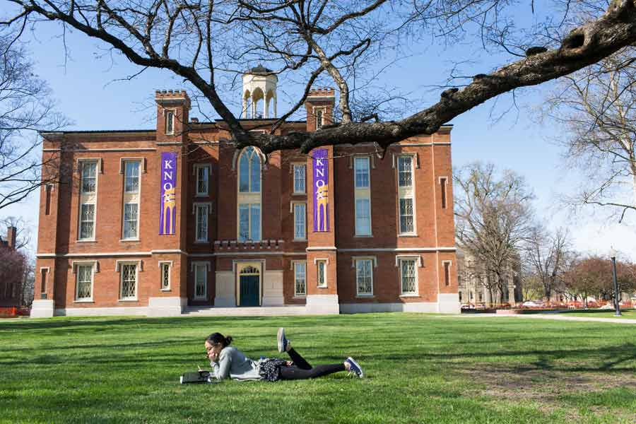 Students loung on the grass outside Old Main on a sunny afternoon.