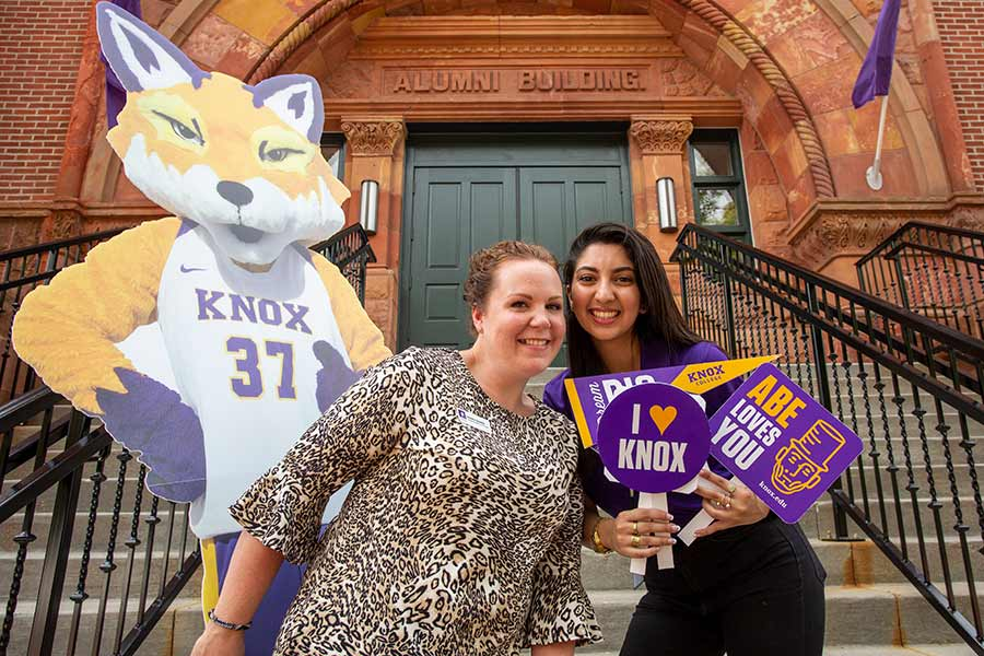 Two admission ambassadors pose for a photo with a cutout of Blaze, the Prairie Fire mascot, on the front steps of Alumni Hall.