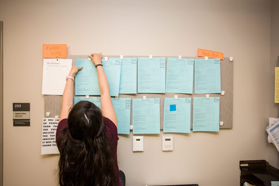 Student in Kleine Center for Community Service, posting volunteer service opportunities on bulletin board; 2017.